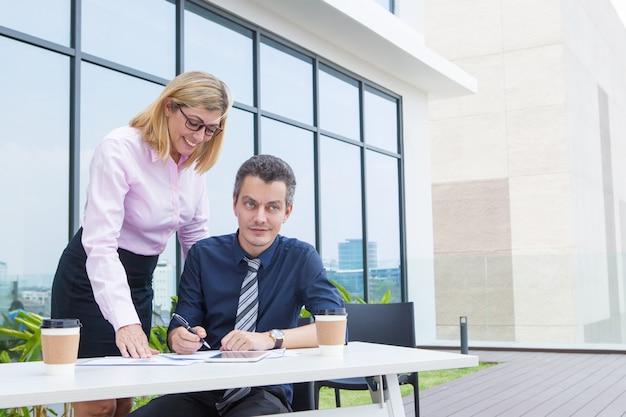 Assistente fêmea positivo que explica o relatório ao trabalhar com o gerente masculino no balcão