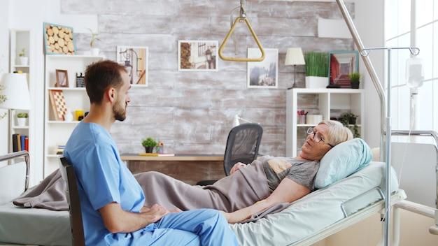 Assistente masculino tomando um assento perto da cama de hospital de uma senhora doente deitada em uma casa de repouso com janelas grandes e brilhantes.