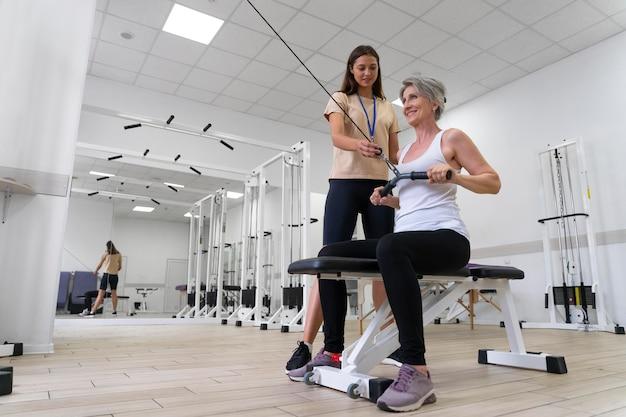 Assistente médico ajudando paciente com exercícios de fisioterapia