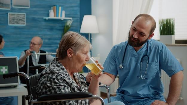 Assistente médico dando vidro com vitamina efervescente ao paciente