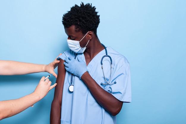 Assistente médico sendo vacinado pelo médico