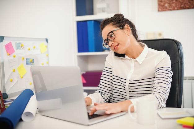 Assistente ocupado falando ao telefone e usando o laptop. interior do escritório.