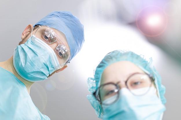Assistente passa o instrumento para o cirurgião na sala de cirurgia
