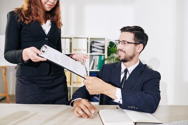 Assistente pedindo sorridente jovem empresário de óculos para assinar documento