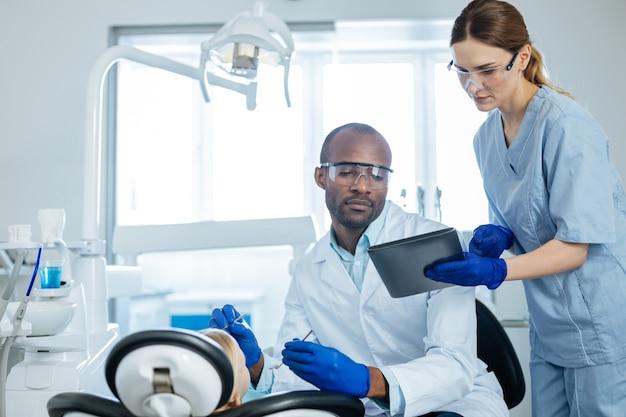 Assistente prestativo. encantadora jovem enfermeira mostrando um aviso sobre a próxima consulta no tablet para o dentista realizando um exame de cavidade oral