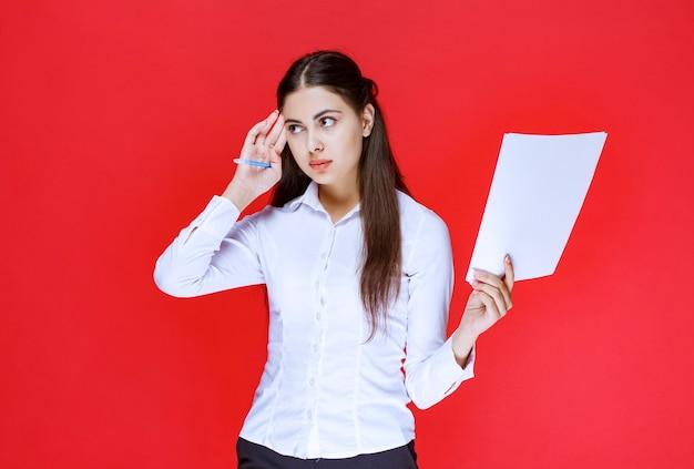 Assistente segurando listas de relatórios e pensamento.