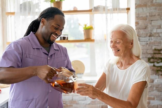 Assistente social africana ajudando uma mulher idosa