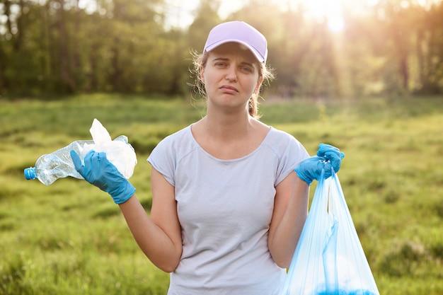 Assistente social, catando lixo no campo, vestindo casualmente, segurando o saco de lixo, cansado, com expressão facial chateada, limpando o parque inteiro, resolvendo problemas ambientais.