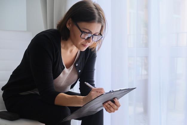 Assistente social da mulher de idade, psicólogo sentado perto da janela com placa de recorte