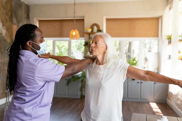Assistente social masculino cuidando de uma velha