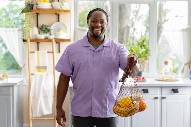Assistente social segurando algumas frutas e vegetais
