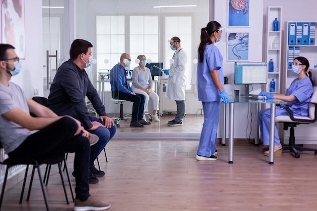 Assistentes médicos conversando na recepção do hospital usando máscaras de proteção contra o vírus covid 19 enquanto os pacientes aguardam o exame