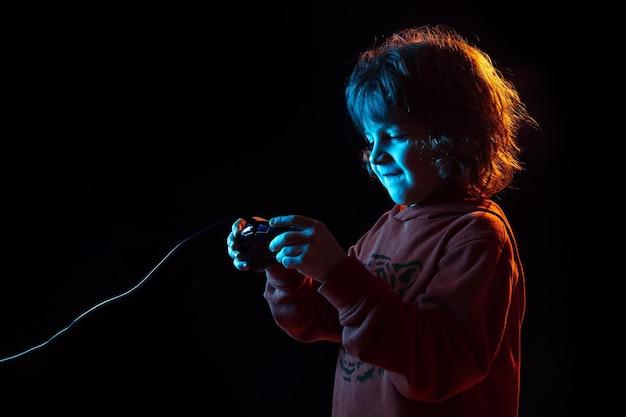Assistido jogando videogame. retrato do menino caucasiano em fundo escuro do estúdio em luz de néon. lindo modelo cacheado.
