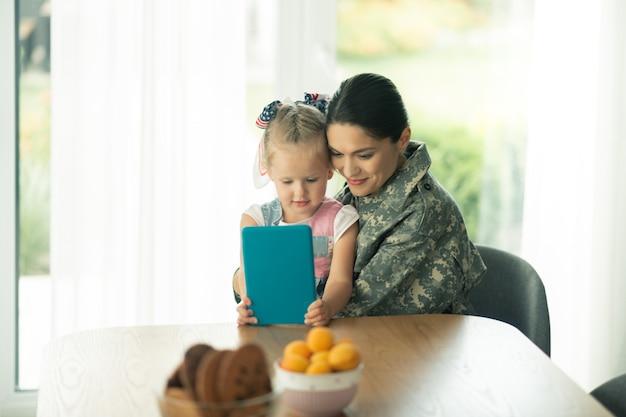 Assistindo desenho animado. filha sentada perto da mãe usando uniforme militar e assistindo desenho animado no tablet