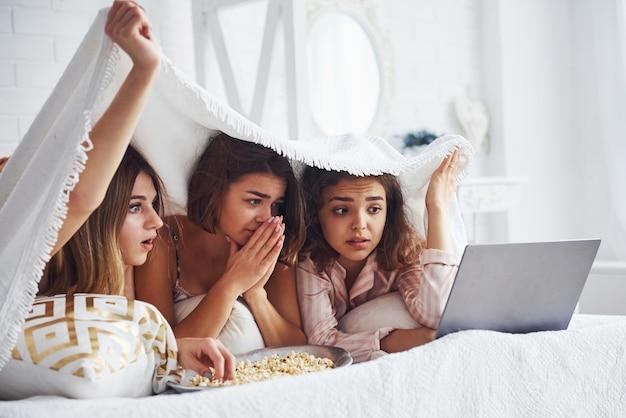 Assistindo filme de terror. felizes amigas se divertindo na festa do pijama no quarto.