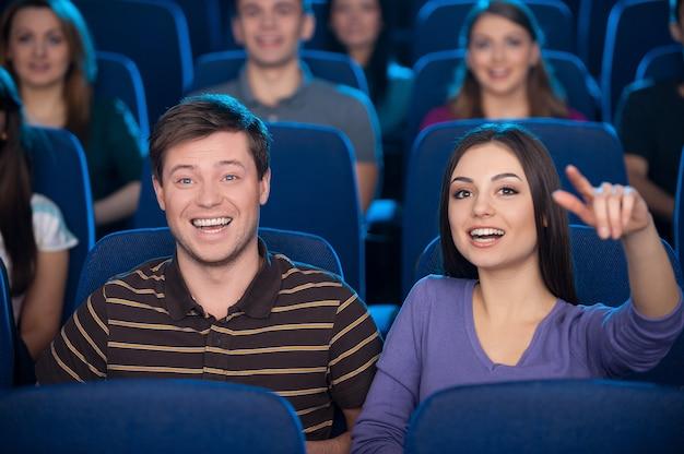Assistindo filme juntos. jovem casal feliz comendo pipoca e bebendo refrigerante enquanto assiste a um filme no cinema
