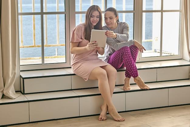 Assistindo filme online em tablet digital por duas mulheres de pijama sentadas no parapeito da janela