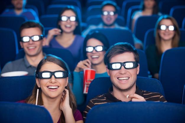 Assistindo filme tridimensional. jovens felizes em óculos tridimensionais assistindo filme no cinema juntos