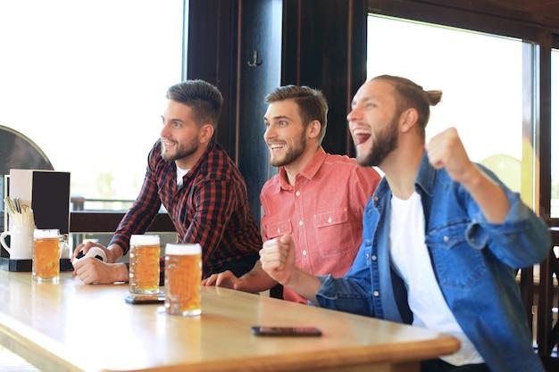 Assistindo futebol no bar. amigos felizes bebendo cerveja e torcendo pelo time favorito, comemorando a vitória.