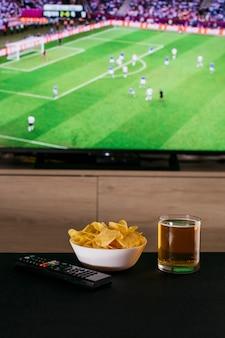 Assistindo o conceito de futebol com cerveja e batatas fritas