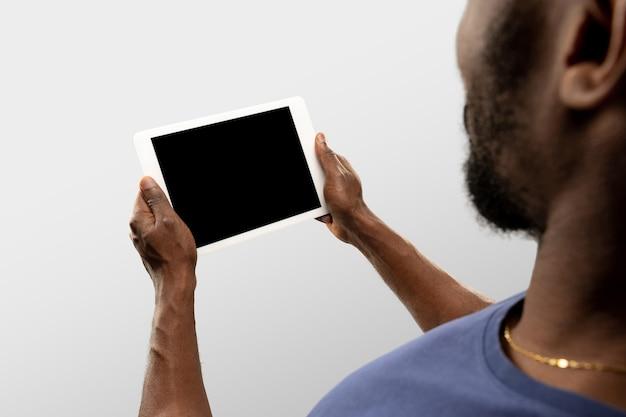 Assistindo, rolando. feche as mãos masculinas segurando um tablet com tela em branco durante a exibição on-line de jogos de esporte popular, campeonatos. copyspace para anúncio. dispositivos, gadgets, conceito de tecnologias.