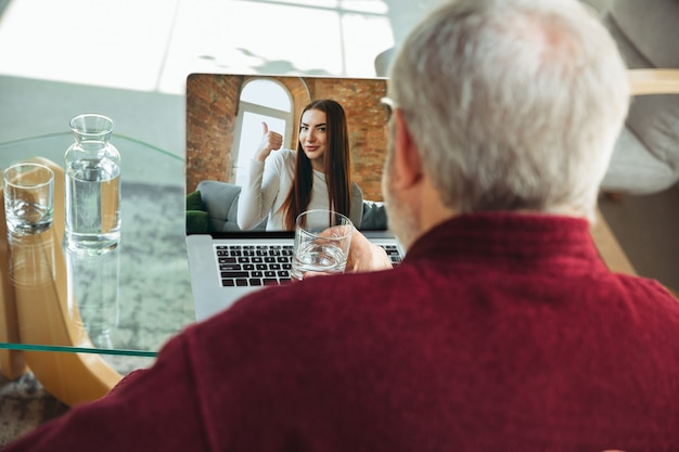 Assistindo show online. homem sênior durante a quarentena, percebendo a importância de ficar em casa durante o surto do vírus. conceito de bloqueio de coronavírus, auto-isolamento, saúde, segurança, proteção.