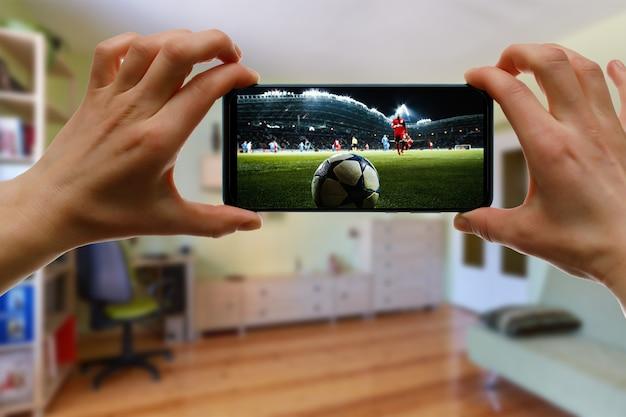 Assistir a um jogo de futebol em casa via smartphone. transmitindo futebol do estádio.