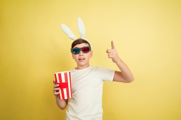 Assistir ao cinema de óculos com pipoca. menino caucasiano como um coelhinho da páscoa em fundo amarelo. feliz páscoa. lindo modelo masculino. conceito de emoções humanas, expressão facial, feriados. copyspace.