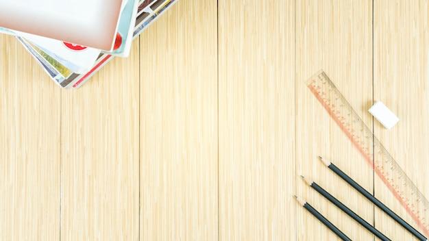 Assoalho de madeira com espaço e decorado com artigos de papelaria e livros.