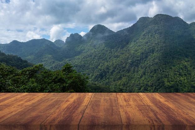 Assoalho de madeira marrom com montanha verde.