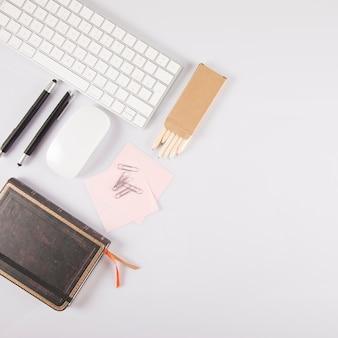 Assorted artigos de papelaria perto de novo teclado e mouse