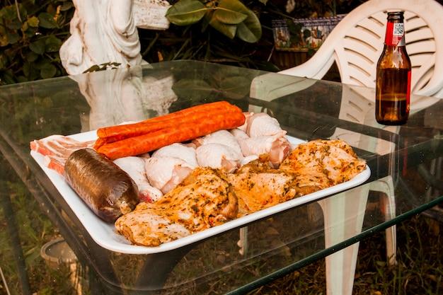 Assorted carne crua na bandeja sobre a mesa de vidro
