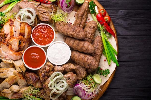 Assorted carne grelhada e legumes na mesa rústica