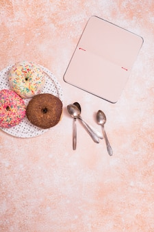 Assorted donuts com chocolate fosco; rosa vitrificada e polvilha donuts na colher de chapa branca e caderno em branco contra o pano de fundo rústico