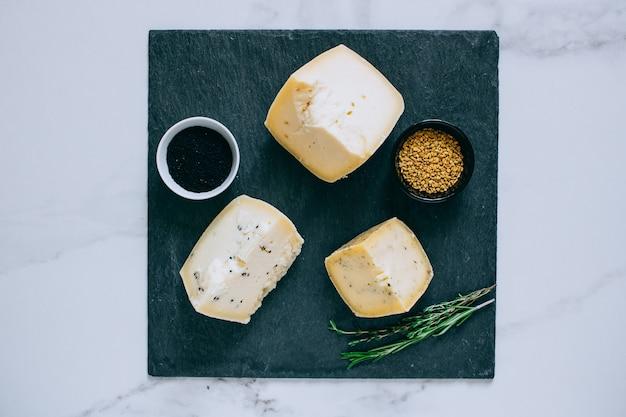 Assorted queijo achotta com cominho preto, feno-grego e ervas no xisto preto