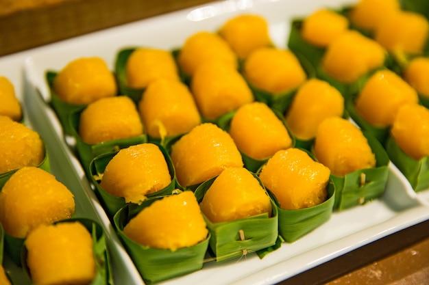 Assorted sobremesa tailandesa (tanga yip) na folha de bananeira em chapa branca