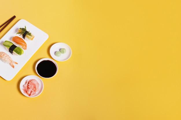 Assorted sushi e condimentos em amarelo