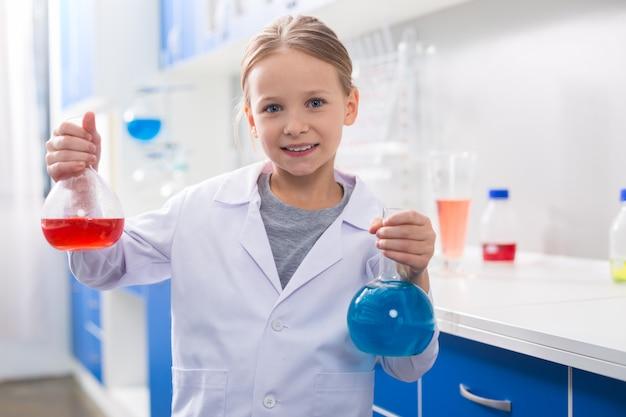 Assunto favorito. positiva linda garota legal segurando frascos e olhando para você enquanto se interessa por química