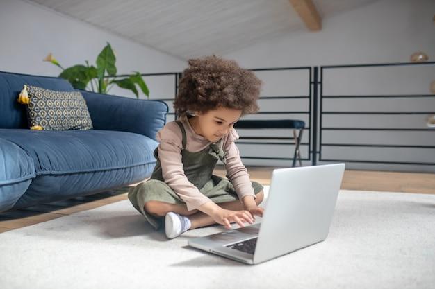 Assunto importante. garotinha de pele escura séria de mãos dadas acima do teclado do laptop, sentada no chão em um belo quarto moderno