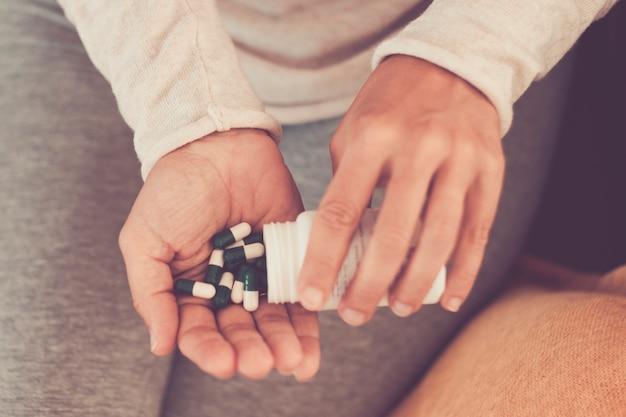 Assunto medicina saúde e produtos farmacêuticos. mãos de mulher caucasiana jovem macro close-up, retirando uma bolha verde. embalando duas pílulas redondas brancas em roupas de casa em casa na cama.