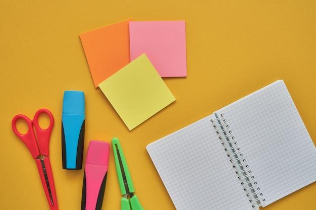 Assuntos escolares em um fundo amarelo. volta ao conceito de escola. lay plana, copie o espaço