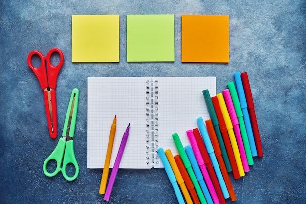 Assuntos escolares sobre um fundo azul escuro. volta ao conceito de escola. bloco de notas, bloco de autocolantes, tesouras coloridas e canetas com ponta de feltro. lay plana, copie o espaço