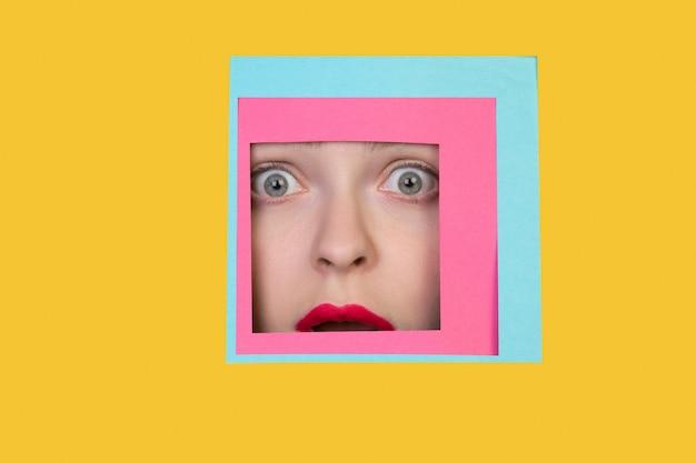 Assustado. o rosto de uma mulher caucasiana emocional espreita toda a praça em fundo amarelo. estilo geométrico moderno, copyspace. cores vibrantes. conceito de vendas, confins, finanças e negócios. enquadramento.