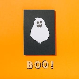 Assustador fantasma em pedaço de papel preto com boo! inscrição abaixo