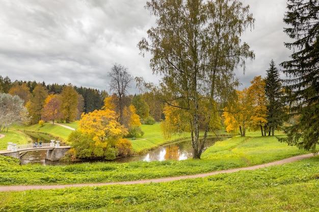 Ast iron bridge a paisagem de outono do parque do palácio de pavlovsk em são petersburgo