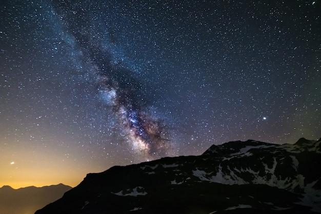 Astro céu noturno, via láctea estrelas da galáxia sobre os alpes, planeta marte e júpiter, cordilheira coberta de neve