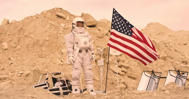 Astronauta com a bandeira americana em pé nas montanhas rochosas do planeta vermelho alienígena / marte. primeira missão tripulada em marte