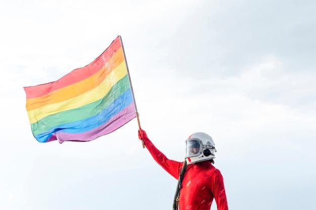 Astronauta com capacete segurando uma bandeira do orgulho gay.