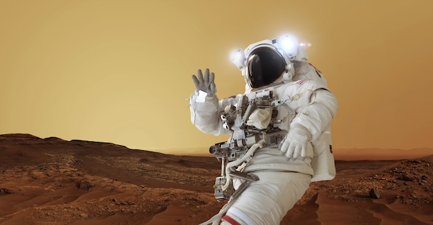 Astronauta em um traje espacial e um capacete com luz fica no planeta vermelho marte cumprimenta e acena com a mão. bem-vindo ao conceito de marte. o homem do espaço viaja