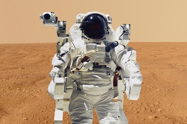 Astronauta fazendo sua missão pousar no planeta marte. sistema solar b. elementos desta imagem fornecidos pela nasa